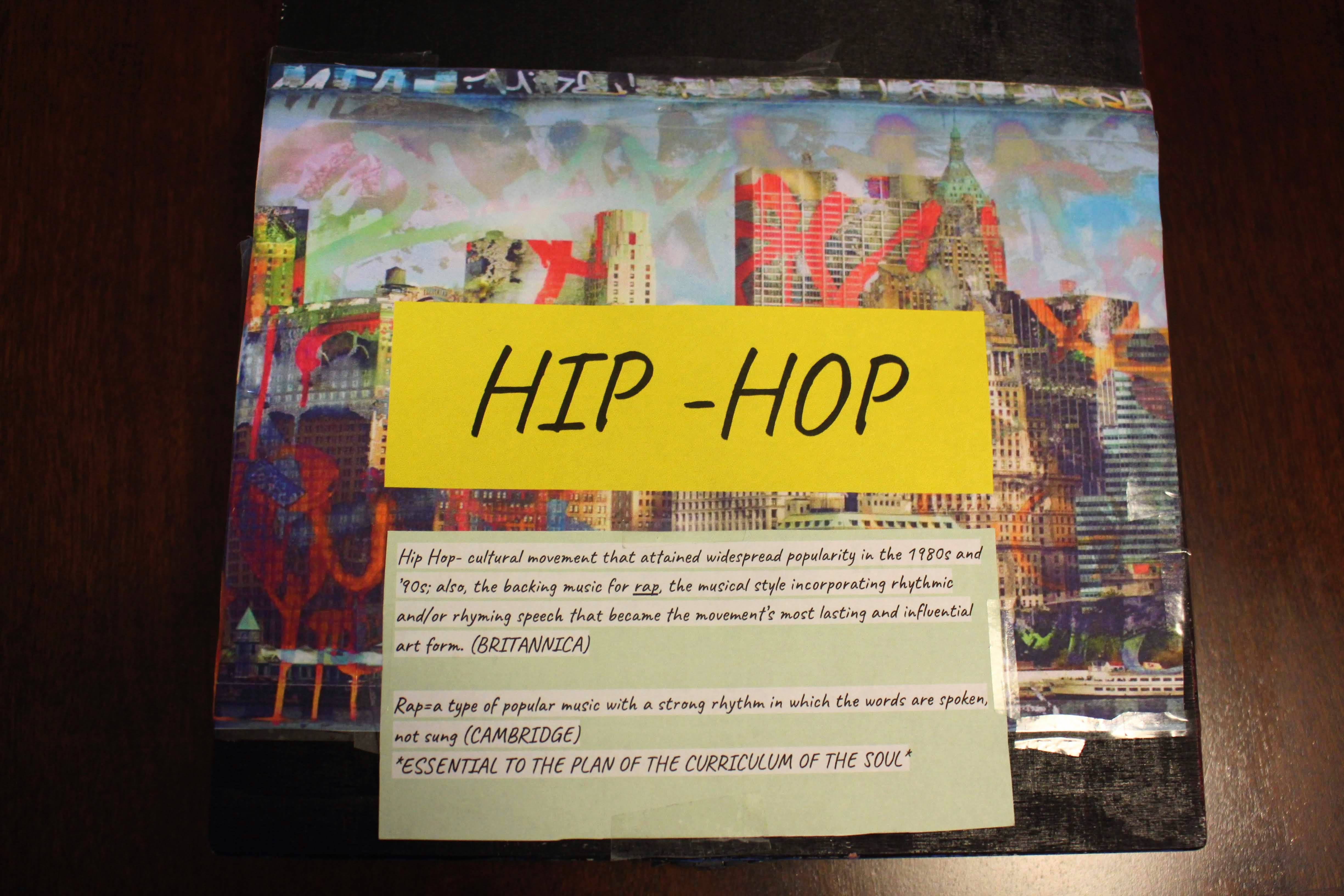 "The top of the Hip-Hop keepsake box. Acrylic on wood. On the top of the box is a cutout of Derek Prospero's ""Graffiti City"" .Placed on top the wallpaper are definitions for 'hip-hop' and 'rap' from Brittanica and Cambridge."