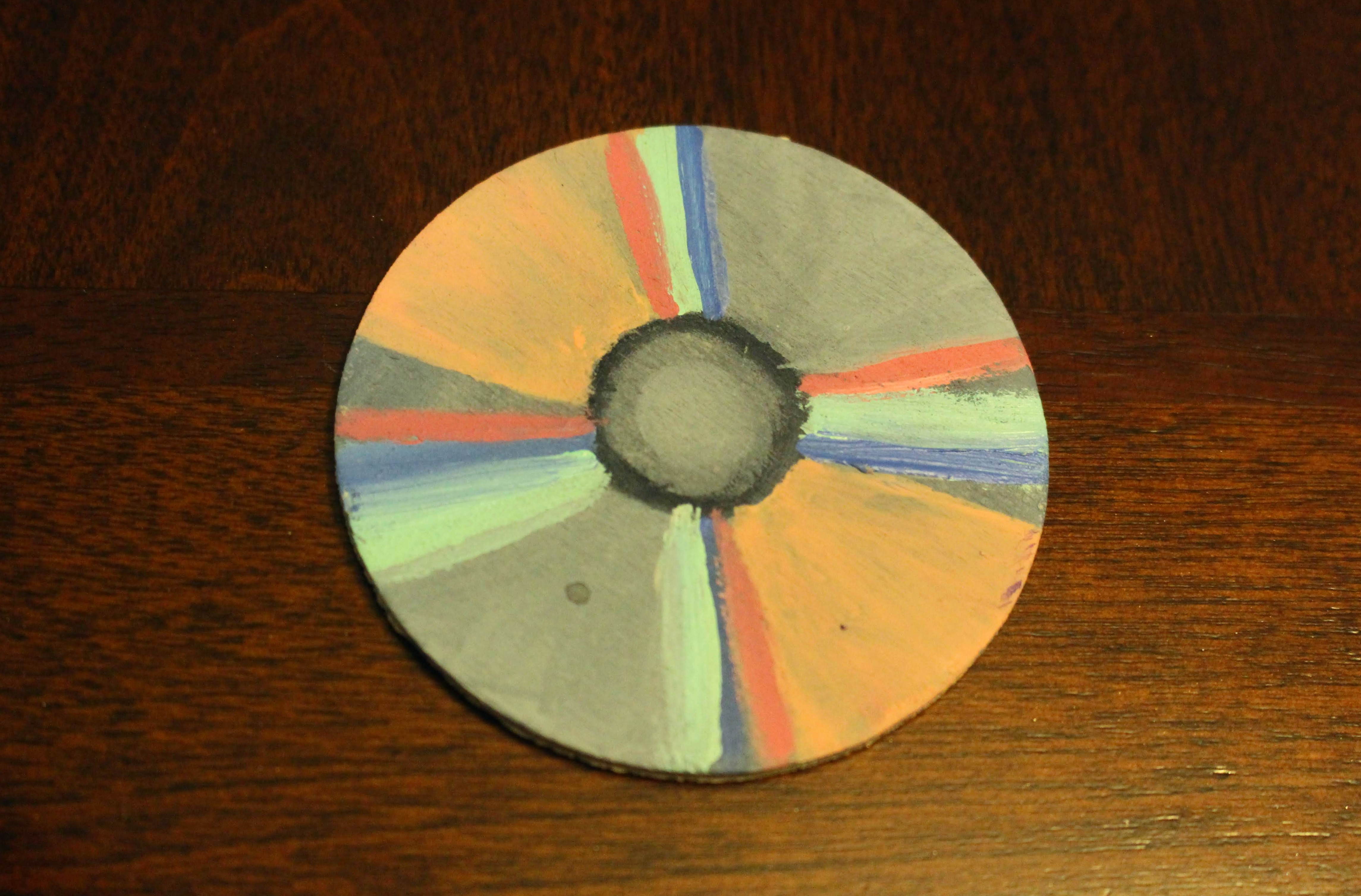 This is a painting of a CD. This was created from using acrylic on wood. This is a part of four other pieces in the kit which represent five types of devices that we used to consume hip-hop throughout the times. The CD in particular I associated with the 1990s.