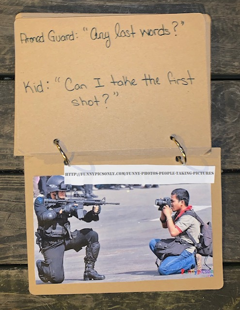 "Page 15 - ""Armed Guard : 'Any last words?' Kid : 'Can I take the first shot?'"" Satire-style photo caption for following photo. (See next page) Page 16 - I found this photo on a website titled ""Funny Pictures,"" but found nothing funny about it. It was actually quite moving. In the photo, a young boy with his backpack holds up his camera to an armed guard (possibly military personnel) who is holding up a rifle, pointed directly back at the young man. It seems like a very intense moment - even if it's only all in the name of photography. I thought of each men and their completely different paths, each holding their choice of weapon."